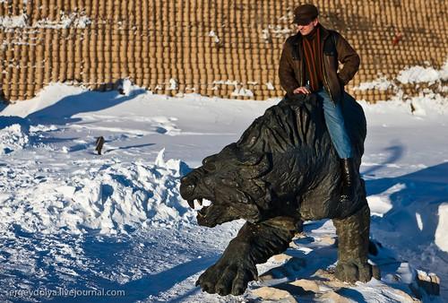 Мужчина сидит верхом на скульптуре.
